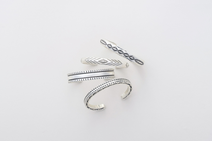 """Stanley Parker (From the top)<br /> Stamped Half Round Wire Bracelet<br /> PRICE / 41,800+tax<br /> <br /> Stamped Triangle Wire Bracelet<br /> PRICE / 39,800+tax<br /> <br /> 1/2"""" Chisel Work Bracelet<br /> PRICE / 37,800+tax<br /> <br /> Chisel Design Square Wire bracelet<br /> PRICE / 39,800+tax"""